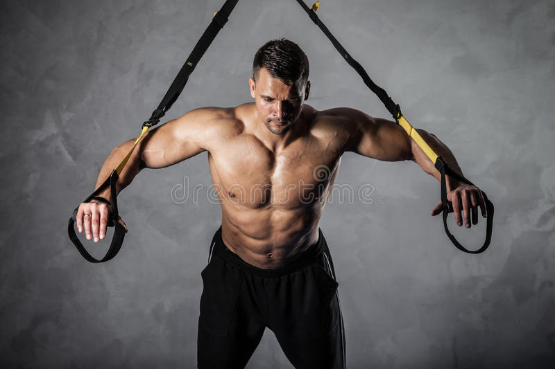 Fitness on crossover. Brutal athletic man pumping up muscles on crossover royalty free stock images