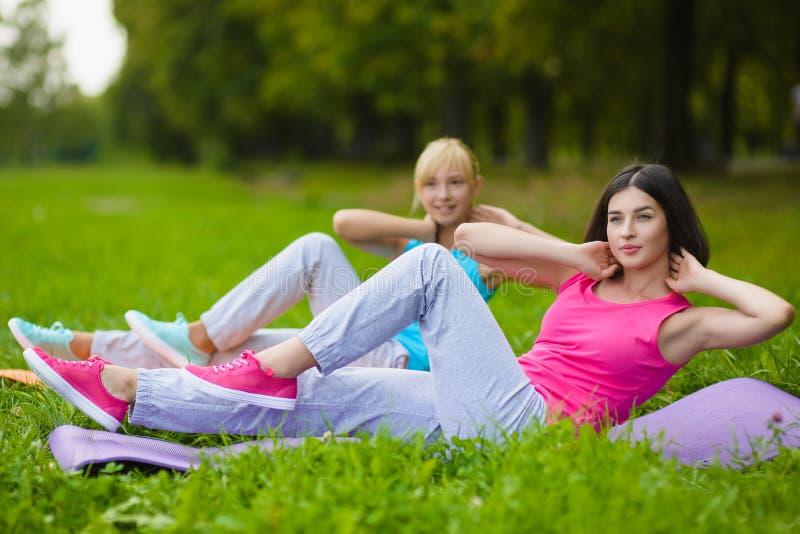 Fitness de sportmeisjes in sportkleding die yogafitness doen oefenen openlucht uit royalty-vrije stock afbeeldingen