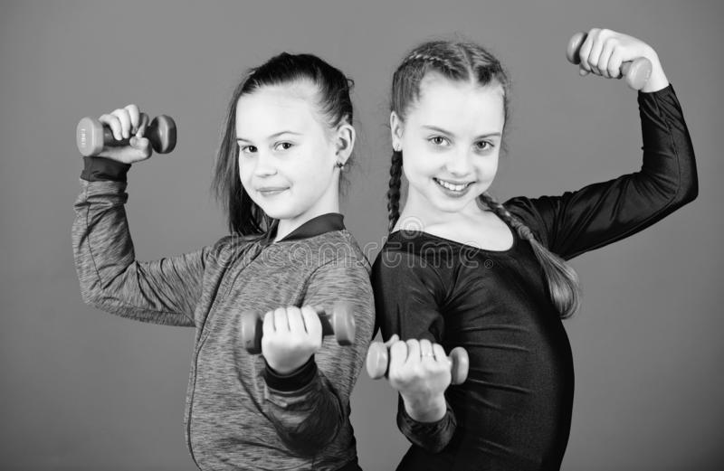 Fitness diet for energy health. triceps workout of small girls hold dumbbell. Sport success. weight lifting for muscules royalty free stock photos