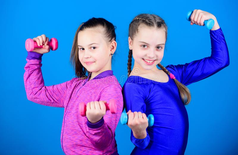 Fitness diet for energy health. triceps workout of small girls hold dumbbell. Sport success. weight lifting for muscules. Happy children sportsman with barbell royalty free stock photo