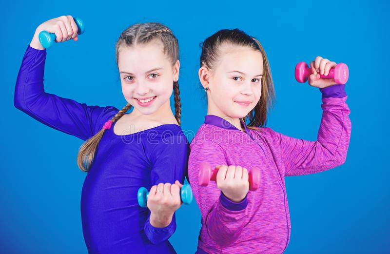 Fitness diet for energy health. triceps workout of small girls hold dumbbell. Sport success. weight lifting for muscules. Happy children sportsman with barbell stock photography