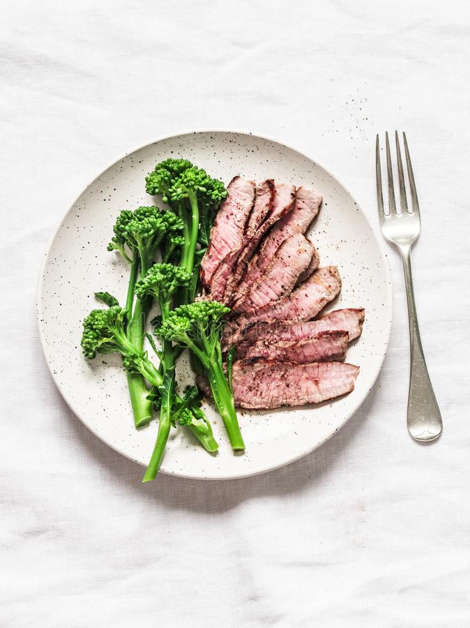 Fitness diet healthy lunch - grilled beef steak and boiled broccoli on a light background, top view royalty free stock image