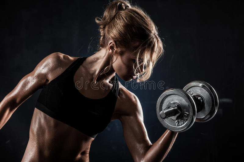 Fitness with dumbbells. Brutal athletic woman pumping up muscles with dumbbells stock photos