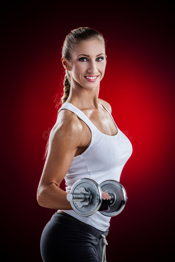 Fitness with dumbbells. Brutal athletic woman pumping up muscles with dumbbells on red background stock image