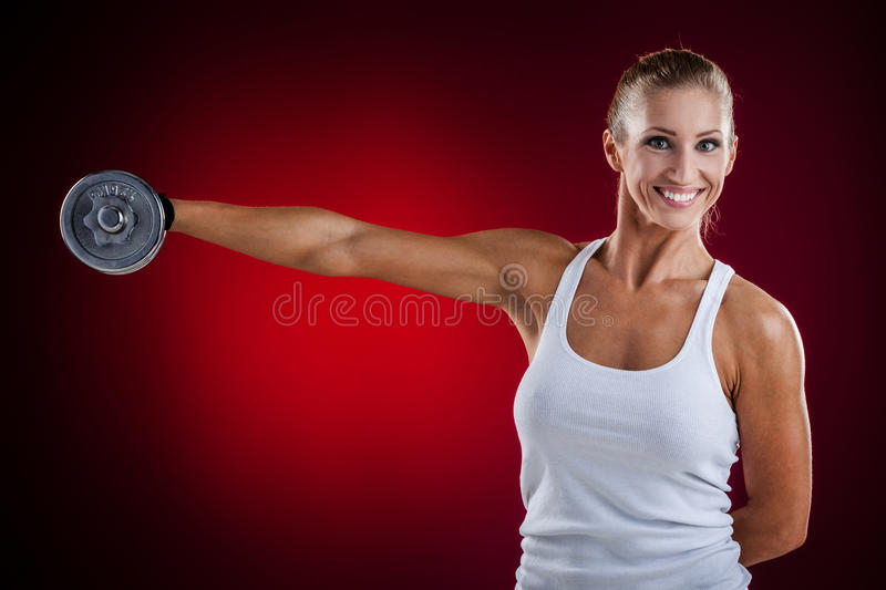 Fitness with dumbbells. Brutal athletic woman pumping up muscles with dumbbells on red background royalty free stock image
