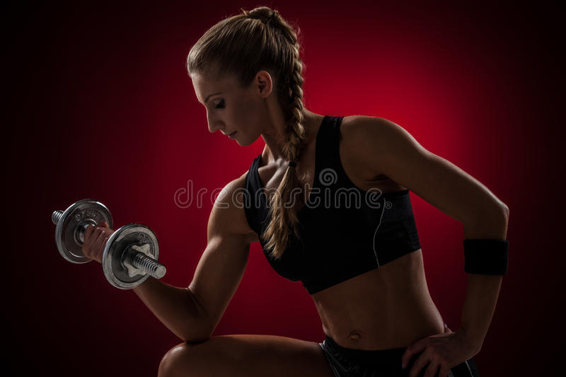 Fitness with dumbbells. Brutal athletic woman pumping up muscles with dumbbells on red background stock photography