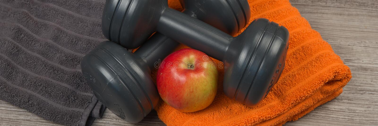 Black Dumbbell and towel with apple. Panorama. Fitness equipment. Black Dumbbell and towel with apple. Panorama royalty free stock photos