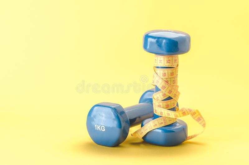 Fitness equipment with blue dumbbells with yellow centimeter/blue dumbbells with centimeter on a yellow background. selective stock photos