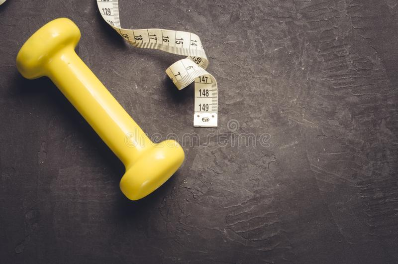 fitness equipment on a dark background/ fitness equipment with yellow dumbbell and measuring tape. Top view and copy space royalty free stock photos