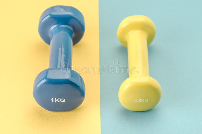 Fitness equipment with dumbbells/blue dumbbell on a yellow background yellow on blue. selective focus royalty free stock images
