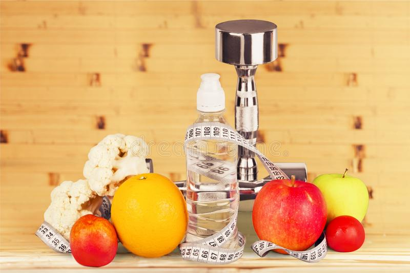 Fitness equipment with fruits and bottle stock photography