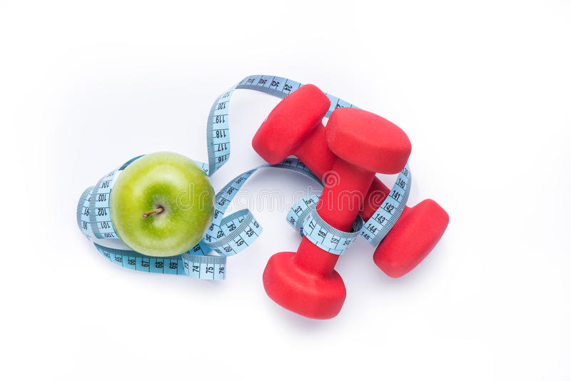 Fitness equipment. Healthy food. Apple, dumbbells and measuring tape on white background. View from above.  stock photos