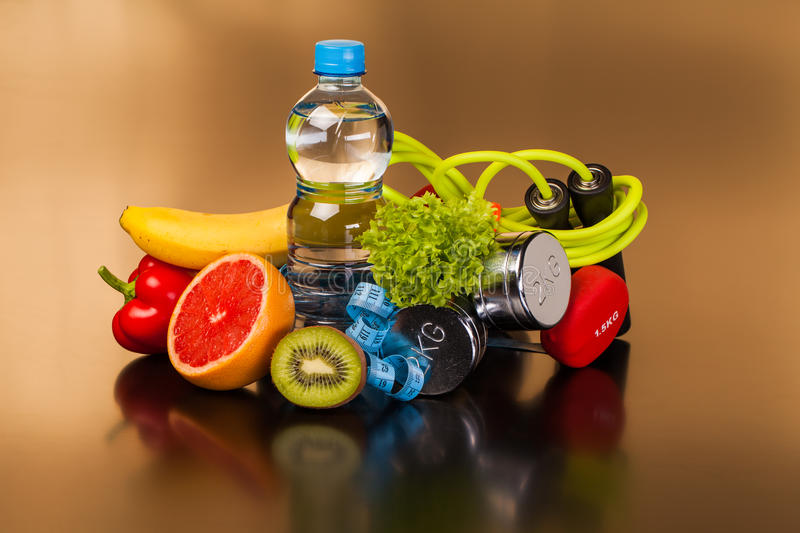 Fitness equipment and healthy food. On black surface royalty free stock images