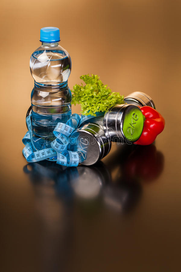 Fitness equipment and healthy food. On black surface stock photography