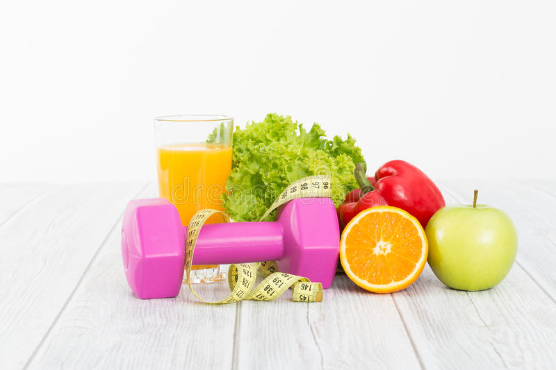 Fitness equipment and healthy food. Fitness concept with dumbbells and healthy food stock images