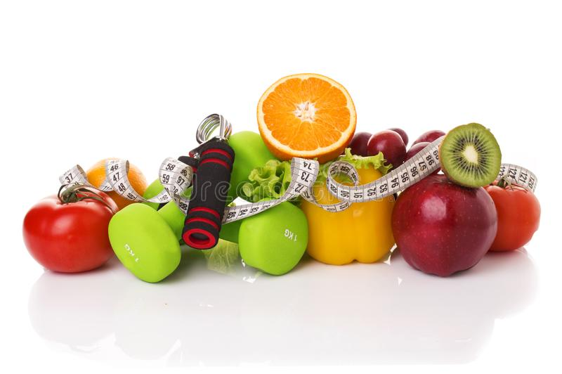 Fitness equipment and healthy food. Isolated on white. apple, pepper, grapes, kiwi, orange, dumbbells and measuring tape royalty free stock images