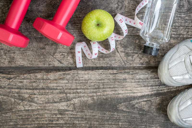 Fitness equipment with healthy food. Over wooden background royalty free stock photos