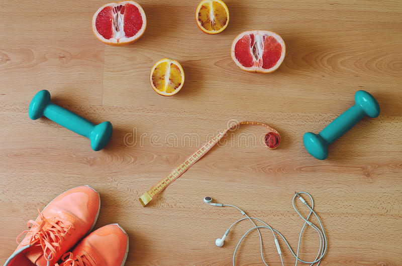 Fitness equipment. Sneakers and health food on wooden background. Flat lay stock photos