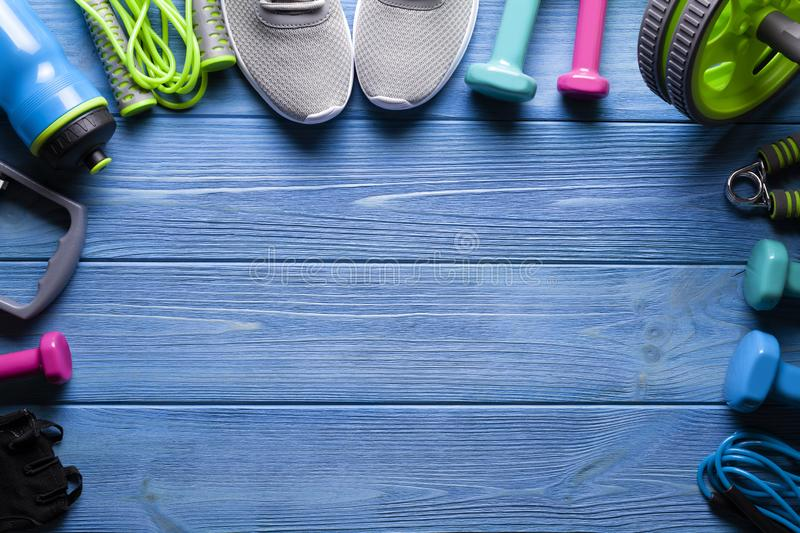 Fitness equipment - sneakers; jumping rope, water bottle and dumbbell on wooden board royalty free stock photography
