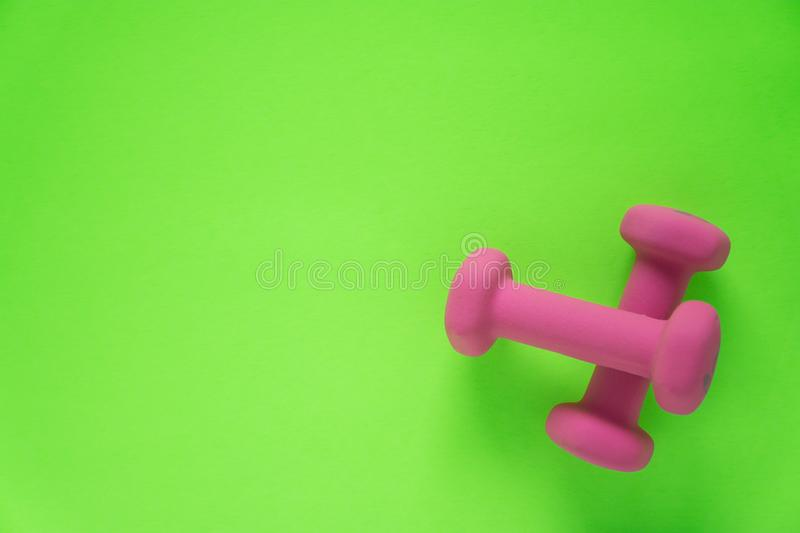 Fitness equipment with womens pink weights/ dumbbells isolated on a lime green background with copyspace. Aka empty text space stock photos