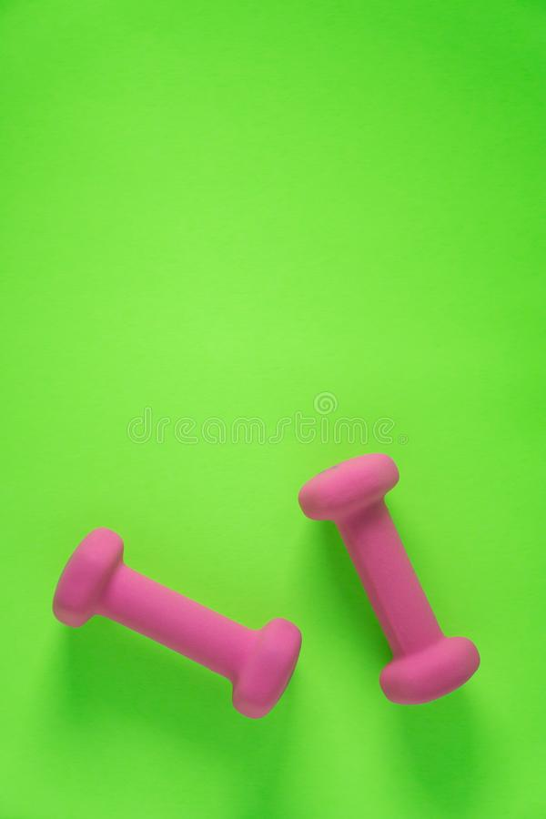 Fitness equipment with womens pink weights/ dumbbells isolated on a lime green background with copyspace. Aka empty text space stock photography