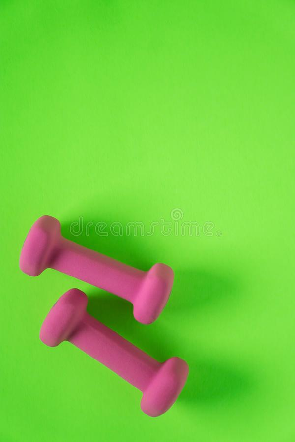 Fitness equipment with womens pink weights/ dumbbells isolated on a lime green background with copyspace. Aka empty text space royalty free stock images
