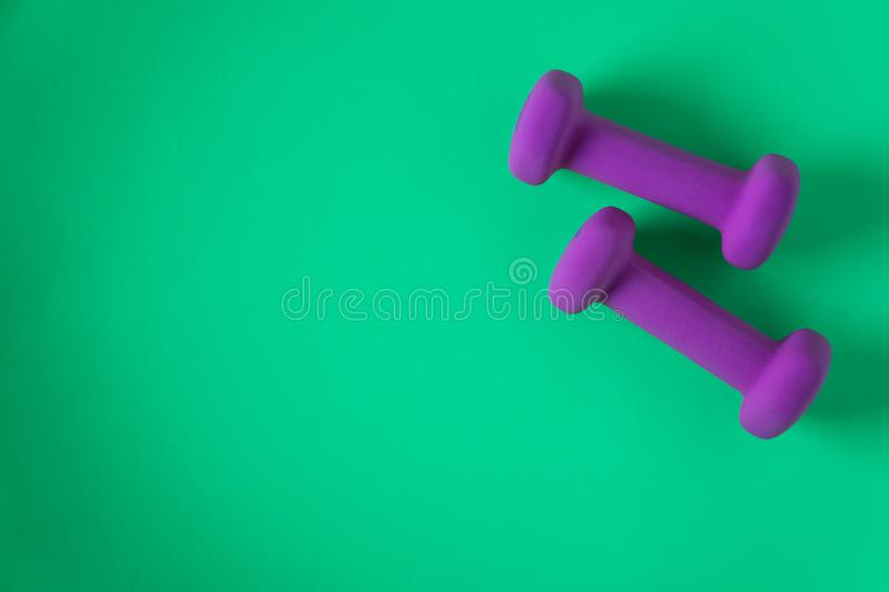 Fitness equipment with womens purple weights/ dumbbells isolated on a teal green background with copyspace royalty free stock photos