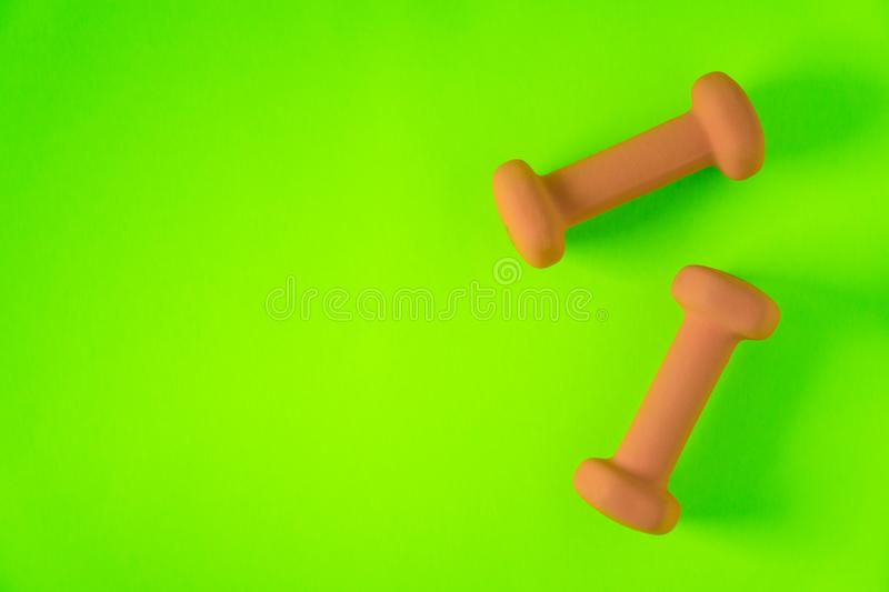 Fitness equipment with womens yellow orange weights/ dumbbells isolated on a lime green with copyspace background with copyspace. Fitness equipment with womens royalty free stock image