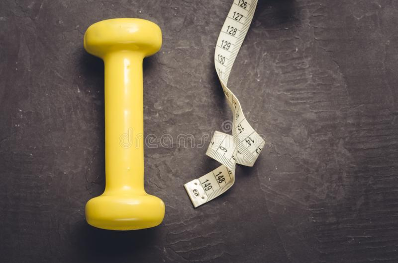fitness equipment with yellow dumbbel on a dark background/ fitness equipment with yellow dumbbell and measuring tape. Top view royalty free stock photography