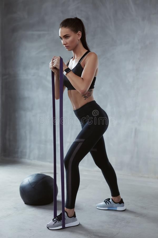 Fitness Exercise. Sports Woman Exercising With Resistance Band. In Fashion Clothes, Loop Workout. High Resolution royalty free stock images