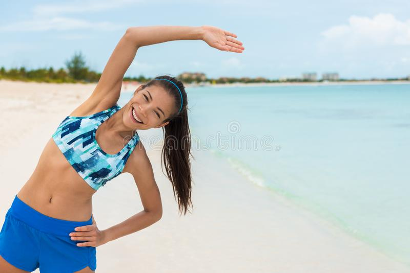 Fitness exercise woman stretching during yoga or pilates class on beach. Happy Asian girl exercising outdoors wearing sports bra stock photo