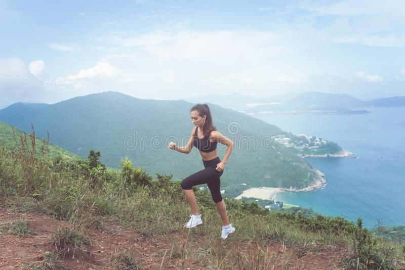 Fitness female athlete wearing black sportswear doing cardio exercise, running in mountains with inspirational sea view stock photo