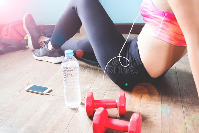 Fitness female in black pants and sneakers relaxing after workout with dumbbells and water. Fitness female in black pants and sneakers relaxing after workout stock image