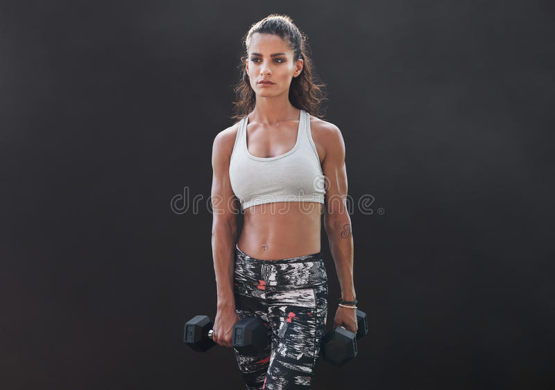 Fitness female doing bodybuilding training with weights. Woman exercising with dumbbells over black background royalty free stock images