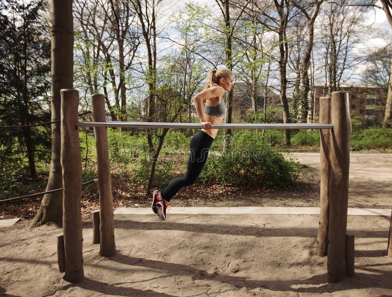 Fitness female doing parallel bar dips. Side view of muscular young woman doing triceps dips on parallel bars at park. Caucasian female fitness model exercising stock photography