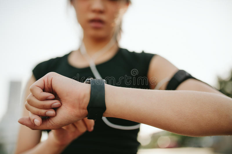 Fitness female monitoring her performance on smartwatch. Close up shot of young sportswoman using smartwatch to track her workout performance. Fitness female royalty free stock photography
