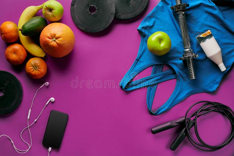 Fitness female outfit background top view. Set of sport clothing and equipment for women, active lifestyle royalty free stock photos