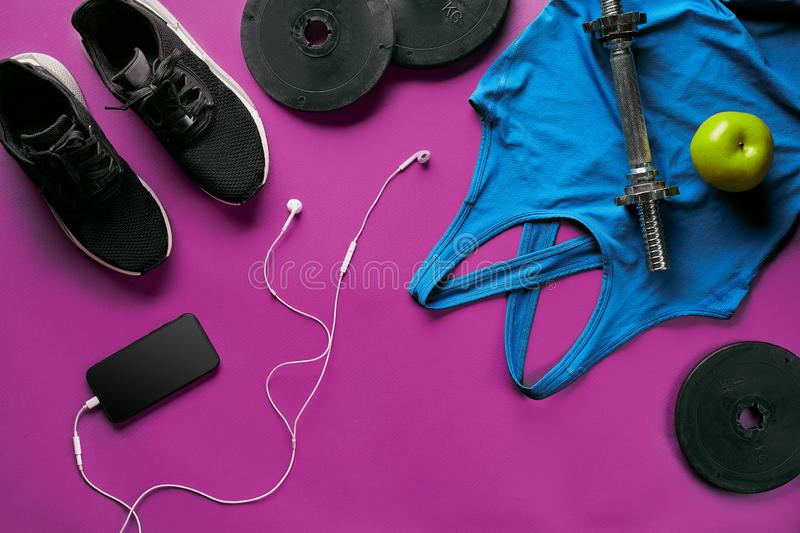 Fitness female outfit background top view. Set of sport clothing and equipment for women, active lifestyle royalty free stock photography