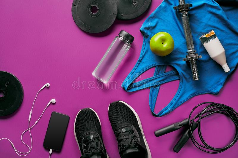 Fitness female outfit background top view. Set of sport clothing and equipment for women, active lifestyle royalty free stock image