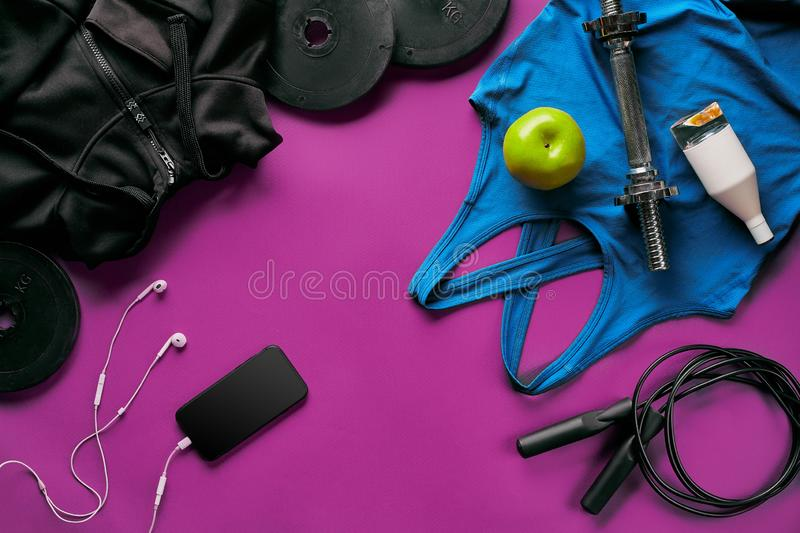 Fitness female outfit background top view. Set of sport clothing and equipment for women, active lifestyle stock photo