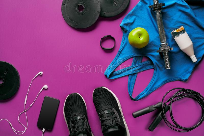 Fitness female outfit background top view. Set of sport clothing and equipment for women, active lifestyle stock images