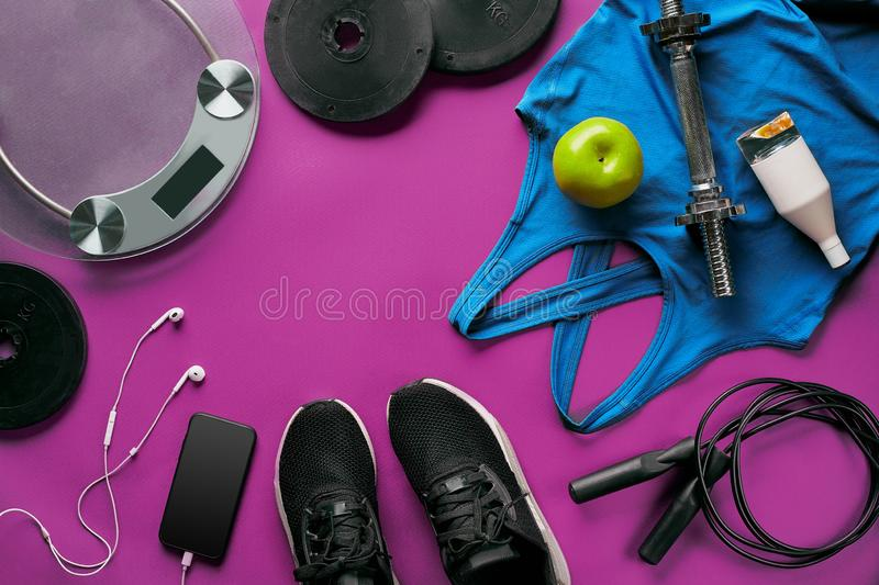 Fitness female outfit background top view. Set of sport clothing and equipment for women, active lifestyle stock photos