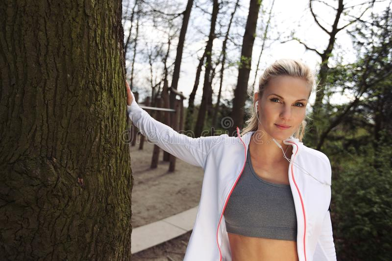 Fitness female resting after outdoors training. Pretty young woman standing by a tree at park. Attractive fitness female resting after outdoors training stock photography