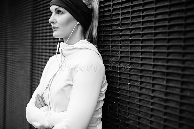 Fitness female taking a break for training session. Black and white image of young woman wearing earphones standing leaning a wall looking away confidently stock photography