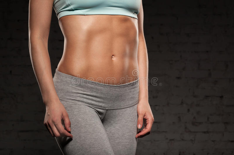 Fitness female woman with muscular body, do her workout, abs, abdominals royalty free stock photo