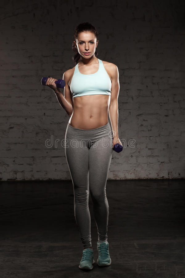Fitness female woman with muscular body, do her workout with dumbbells. Fitness female woman with muscular body do her workout with dumbbells royalty free stock photo
