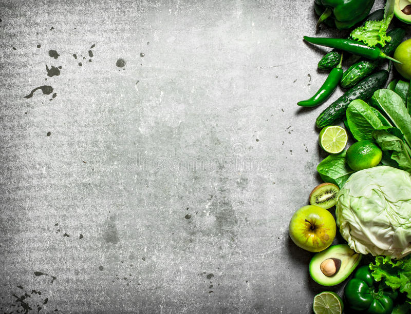 Fitness food. Green vegetables and fruits. On the stone table stock images