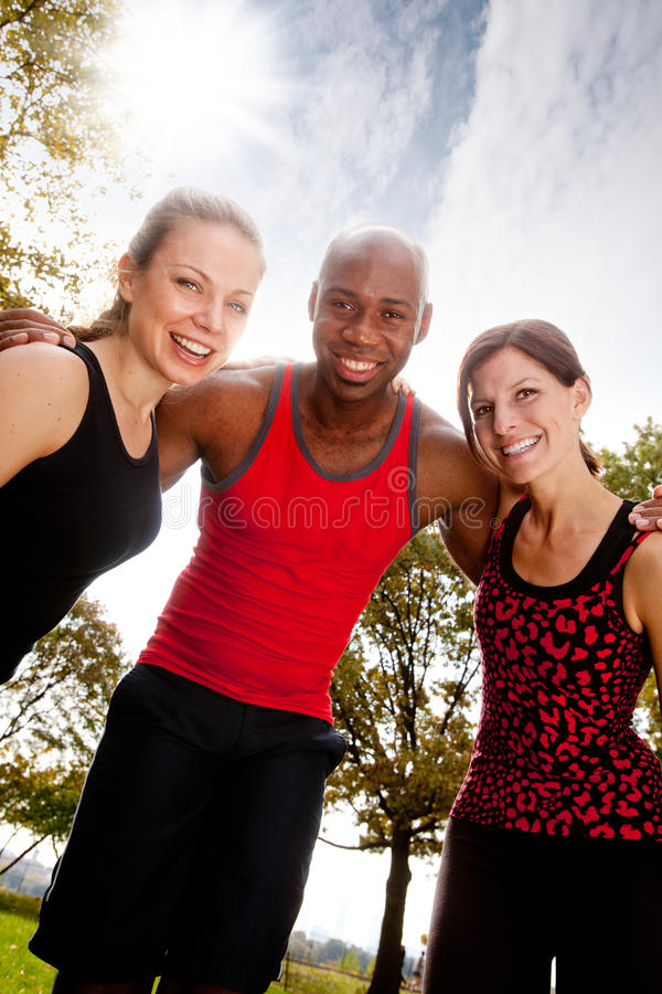 Fitness Friends. A group of frIends exercising in the park on a warm sunny day stock image