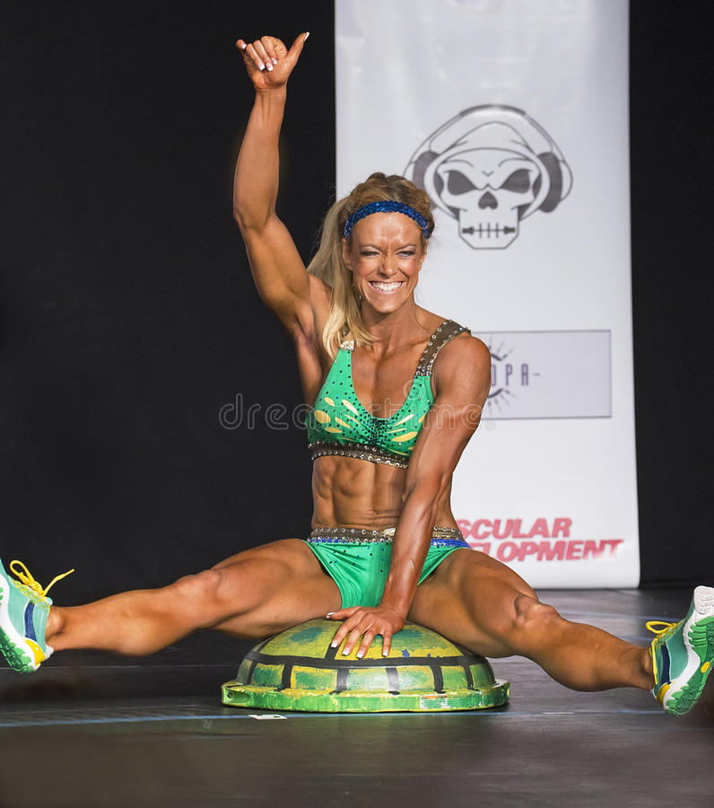 Fitness Gal on a Turtle Shell. Buff Fitness athlete Ashby Smith brings an unusual prop to her stage performance as she competes in the Fitness finals of the 2016 stock images