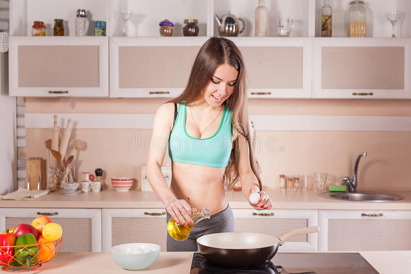 Fitness girl cooking healthy food. At the kitchen royalty free stock image